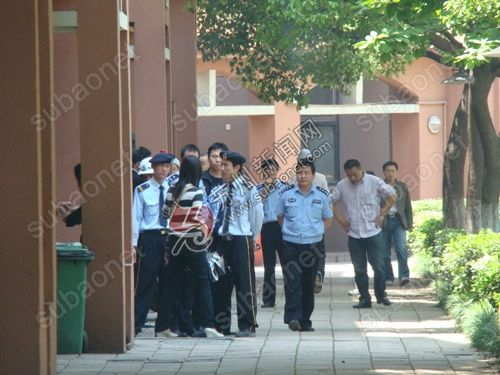 Polce and security guards talk to a journalist near the crime scene at Singha Plaza.